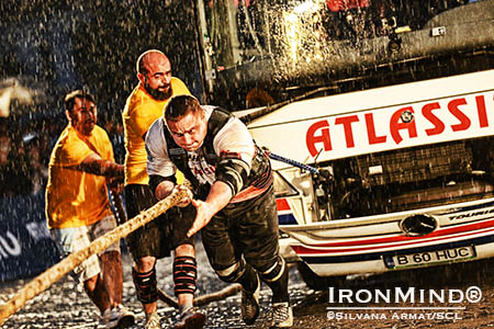 "Ilkka Kinnunen: ""Here is a great shot of the Bus Pull in Romania. As you can see it was raining like hell, but we all survived and the IronMind harness did the job :-)."" IronMind® 