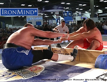 Martins Licis (right) is a favorite to bring back a gold medal from the Mas Wrestling World Championships. The object in mas wrestling is to either pull the stick from your opponent's hands or to pull your opponent over the center board. IronMind® | Courtesy Romark Weiss/Mas USA