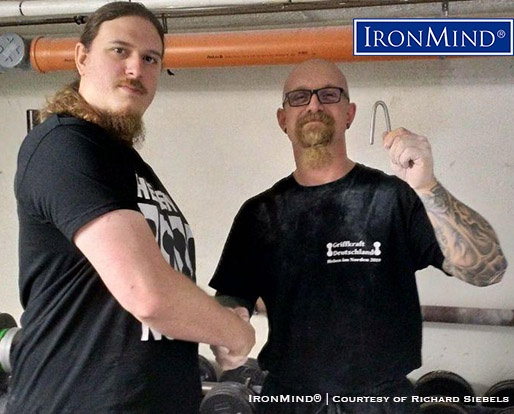 It started off as rehab and grew into a passion for lower arm and grip strength: Richard Siebels (right) has just been certified on the Red Nail, a benchmark short steel bend. Siebel's official attempt to bend an IronMind Red Nail was refereed by Simon Mahalsky (right), who, incidentally, is certified on the Captains of Crush No. 3 gripper. IronMind® | Courtesy of Richard Siebels