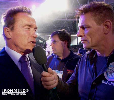 SCL co-founder Marcel Mostert (right) interviewed Arnold Schwarzenegger (left), who presented the winner's check to Zydrunas Savickas.  IronMind® | Courtesy of SCL.