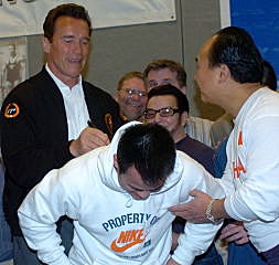 With a little help from Chinese weightlifting coach Chen Wenbin, California Governor Arnold Schwarzenegger autographs Zhang Guozheng's sweatshirt. IronMind® | Randall J. Strossen, Ph.D. photo.