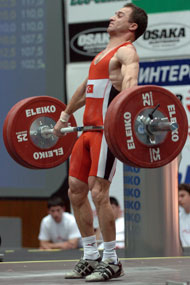 56-kg Sedat Artuc (Turkey) finishing his pull on his third attempt snatch, 125 kg, on his way to victory at the 2005 European Weightlifting Championships. IronMind® | Randall J. Strossen, Ph.D. photo.
