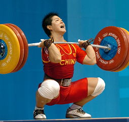 Liu Chunhong (China) hits the bottom with her 153-kg clean and jerk. This lift broke the Olympic, junior world and senior world records in both the clean and jerk and in the total. IronMind® | Randall J. Strossen, Ph.D. photo.