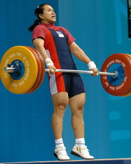 Pawina Thongsuk (Thailand) finishes her pull on this 150-kg clean and jerk, good enough for the gold medal, and an Olympic record in the clean and jerk. IronMind® | Randall J. Strossen, Ph.D. photo.
