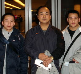 Coach Chen Wenbin (center) and his two Olympic gold medalists, Shi Zhiyong (left) and Zhang Guozheng (right) arrive at Chicago's O'Hare International Airport yesterday. IronMind® | Randall J. Strossen, Ph.D. photo.