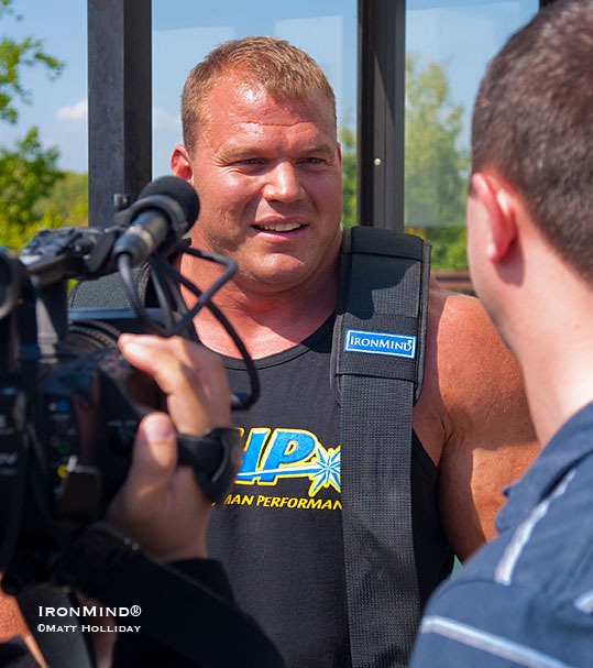 Surrounded by media crews, Derek Poundstone describes his world record bus pull for ESPN, Fox, and Channel 3, as well as local media. IronMind® | Matt Holliday photo.