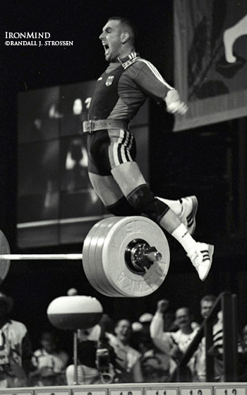 "Can weightlifters jump? Some can nearly fly: 83-kg weightlifter Marc Huster (Germany) celebrates his 213.5 kg world record clean and jerk at the 1996 Centennial Olympic Games (Atlanta) with one of his trademark leaps. Randall Strossen once asked Marc if he ever considered a second career as a high jumper. He said, ""Maybe a kangeroo."" Randall J. Strossen, Ph.D. photo."