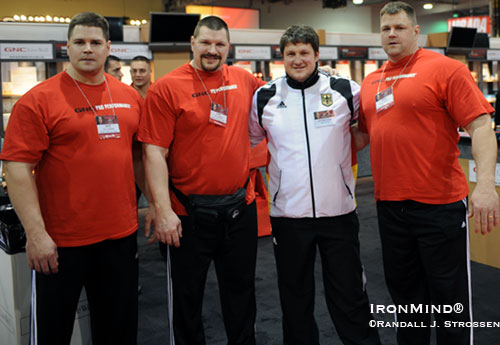 "Left to right: Wade Gillingham, Karl Gillingham, Matthias Steiner, and Brad Gillingham, at the GNC booth at the 2009 Arnold.  Surrounded by around half a ton of Gillinghams, Matthias Steiner - the 2008 super heavyweight Olympic gold medalist in weightlifting said, ""I feel like a little boy.""  Grip strength, strongman, Olympic-style weightlifting and powerlifting - there's a lot of talent in this photo.  IronMind® 