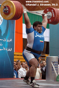 Two-time Olympic gold medalist Hossein Rezazadeh punches up a 260-kg clean and jerk at the 2005 Asian Weightlifting Championships (Dubai, United Arab Emirates). IronMind® | Randall J. Strossen, Ph.D. photo.