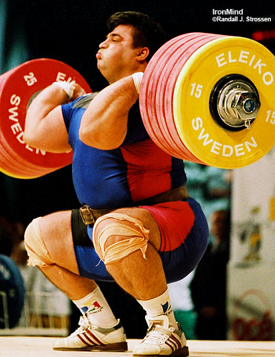 Hossein Rezazadeh hits the bottom with 263 kg, on his way to breaking the world record in the clean and jerk at the 2002 World Weightlifting Championships (Warsaw, Poland). IronMind® | Randall J. Strossen, Ph.D. photo.