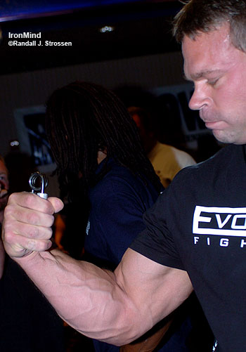 Legendary arm wrestler John Brzenk demonstrates one of his gripper training techniques with a brand new No. 1.5 Captains of Crush® gripper. Look at the Brzenk forearm, which had just mowed down all comers at the International Tournament of Champions at the Boomtown Casino and Hotel. IronMind® | Randall J. Strossen, Ph.D. photo.