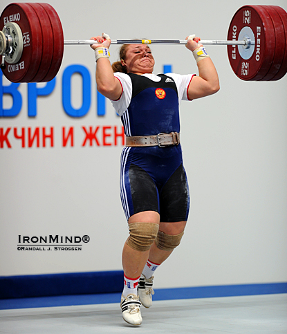 On her way to completing a 181-kg clean and jerk, Tatiana Kashirina drives her body under the bar, splitting her feet front and back.  Kashirina broke two world records in the womens' superheavyweight (+75 kg) category. IronMind® | Randall J. Strossen photo.