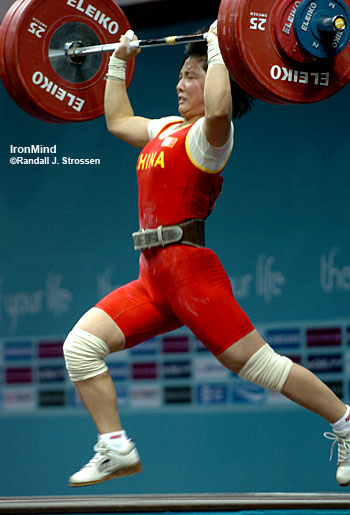 Li Ping (China) drives herself under 129 kg, going for a handful of world records at the Asian Games. She missed the lift, but won the gold medal in the women's 53-kg category. IronMind® | Randall J. Strossen, Ph.D. photo.
