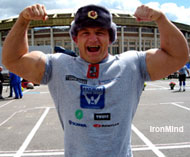 Three-time World's Strongest Man winner Mariusz Pudzianowski, modeling a Russian Army hat, hits a double biceps pose in front of Moscow's Olympic Stadium. IronMind® | Colin Bryce photo.