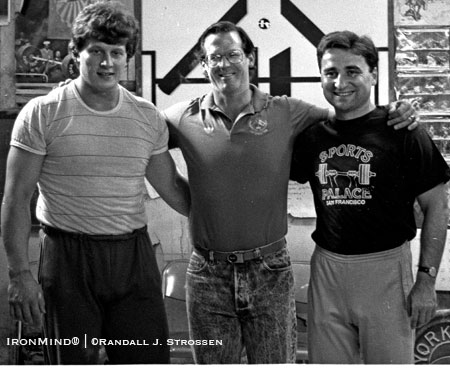 Nicu Vlad (left) and Dragomir Cioroslan (right) were coming to the USA for the 1990 Goodwill Games, so Jim Schmitz (center) organized some coaching clinics, coordinating USAW-NSCA resources. Here, the three men take a break after Nicu's workout in the famous back room at the Sports Palace . . . where Jim Schmitz christened the Romanian Deadlift. IronMind® | Randall J. Strossen photo.