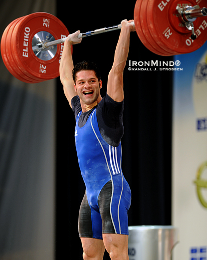 Having just gone six-for-six and pocketing all three gold medals in the men's 69-kg category at the 2010 European Weightlifting Championships, Ninel Miculescu gives his coaches a big smile after punching this 180-kg clean and jerk overhead.  IronMind® | Randall J. Strossen photo.