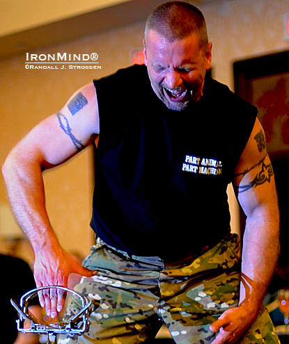Pat Povilaitis shakes hands with a mountain lion trap at the 2008 AOBS dinner.  IronMind® | Randall J. Strossen photo.