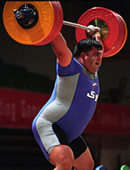 Hossein Rezazadeh (Iran) on his way up with a world record 213-kg snatch at the 2003 Asian Weightlifting Championships (Qinhuangdao, China). IronMind® | Randall J. Strossen, Ph.D. photo.