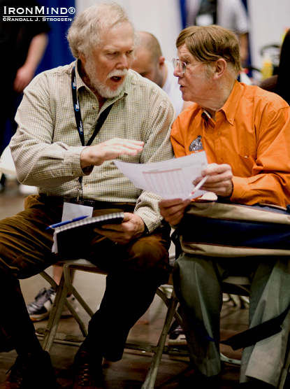 There's a lot of iron game history on tap in those two seats: Dr. Terry Todd (left) and David P. Webster, OBE (right) compare notes as they watch the action at the FitExpo strongman contest (and the grip contest), with the goal of extending the last two invitations open to the 2011 Arnold strongman contest.  IronMind® | Randall J. Strossen photo.