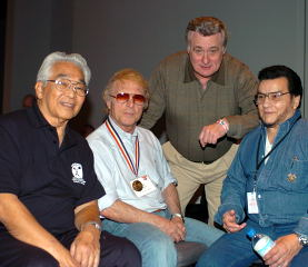 (Left to right) Tommy Kono, Issac Berger, Lou DeMarco and Chuck Vinci relax at the 2004 Arnold. IronMind® | Randall J. Strossen, Ph.D. photo.
