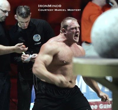 "With Marcel Mostert (center) calmly tabulating the scores, Travis Ortmayer seems to be saying of the stones, ""First I load them . . . and then I eat them!"" Watch the broadcast of the Strongman Champions League contest in Latvia and find out. IronMind® 