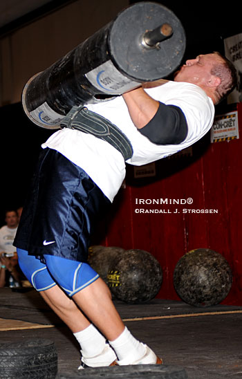 Shown shouldering the 300-pound steel log, so that he can begin punching out the overhead reps, Travis Ortmayer won the contest . . . again. Set on the Jesse Marunde Memorial main stage at the FitExpo, this weekend's All-American Strongman Challenge was a huge hit. IronMind® | Randall J. Strossen photo.