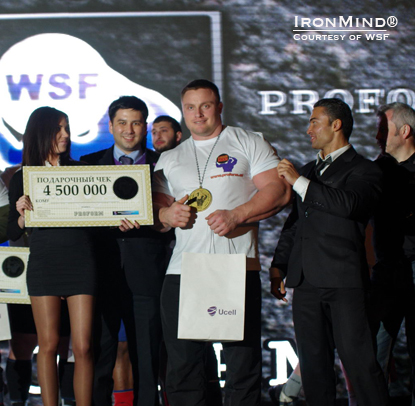 Poland's Krzysztof Radzikowski, who won the WSF Strongman Cup competition in Tashkent, Uzebekistan, is flanked by Timur Sabirov (right) and a Ucell representative (left), with WSF director Vlad Redkin on the far right.  About that check: Are those US dollars?!  IronMind® | Photo courtesy of WSF.