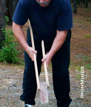 Here John uses a brick instead of a weight plate.  Notice the increased difficulty of the exercise by the placement of the sticks on the brick:  the brick will want to wobble and slip free of the sticks; therefore, you will need to exert more pressure to keep it in place.  IronMind® | Photo courtesy of John Brookfield.